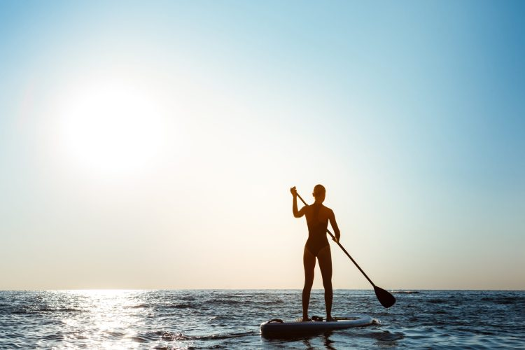 Silhouette of young beautiful girl surfing in sea at sunrise. Outdoors.